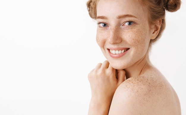 Nahaufnahmeaufnahme der zarten und weiblichen gut aussehenden ingwerfrau, die nackt im profil steht, das mit glücklichem niedlichem lächeln dreht, das bad genießt und sich während des kosmetologischen verfahrens entspannt Kostenlose Fotos