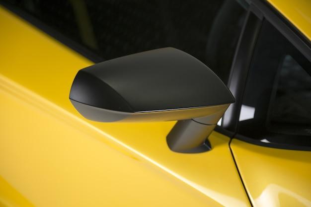 Nahaufnahmeaufnahme des schwarzen seitenspiegels eines gelben modernen sportwagens Kostenlose Fotos