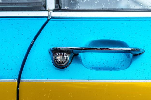 Nahaufnahmeaufnahme des türgriffs eines blauen und gelben autos Kostenlose Fotos