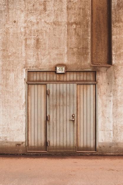 Nahaufnahmeaufnahme einer braunen holztür eines betongebäudes Kostenlose Fotos