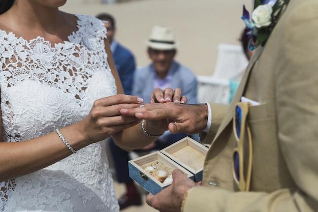 Nahaufnahmeaufnahme einer braut, die einen ehering auf die hand des bräutigams setzt Kostenlose Fotos