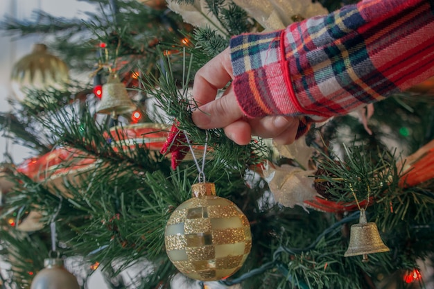 Nahaufnahmeaufnahme einer frau, die einen weihnachtsbaum mit hellen kugeln verziert Kostenlose Fotos