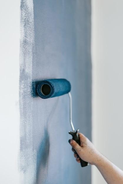 Nahaufnahmeaufnahme einer frau unter verwendung von farbrollern mit der farbe blau Kostenlose Fotos