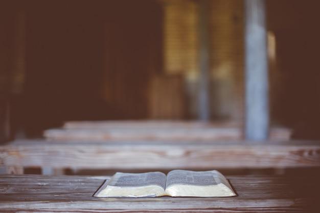 Nahaufnahmeaufnahme einer offenen bibel auf einem holztisch Kostenlose Fotos