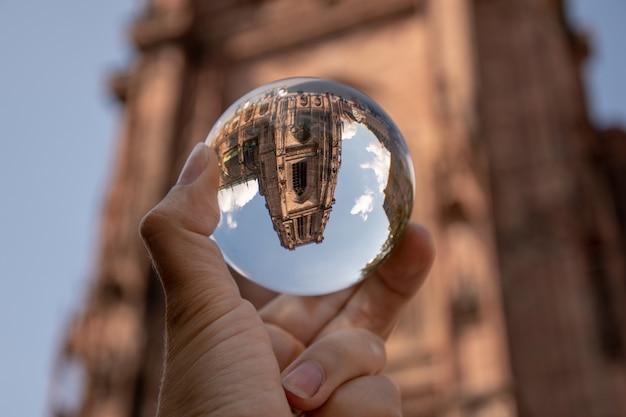 Nahaufnahmeaufnahme einer person, die eine kristallkugel mit dem spiegelbild historischer gebäude hält Kostenlose Fotos