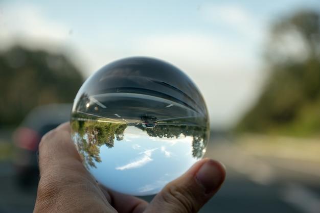 Nahaufnahmeaufnahme einer person, die eine kristallkugel mit der reflexion von bäumen hält Kostenlose Fotos