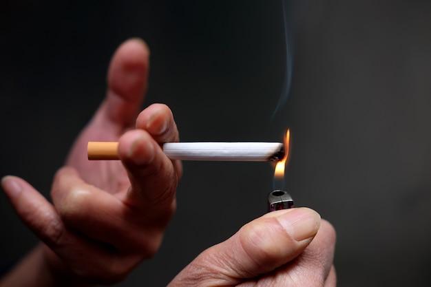 Nahaufnahmeaufnahme einer person, die eine zigarette anzündet Kostenlose Fotos