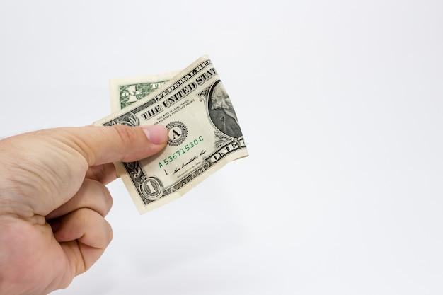 Nahaufnahmeaufnahme einer person, die einen dollarschein über einem weißen hintergrund hält Kostenlose Fotos