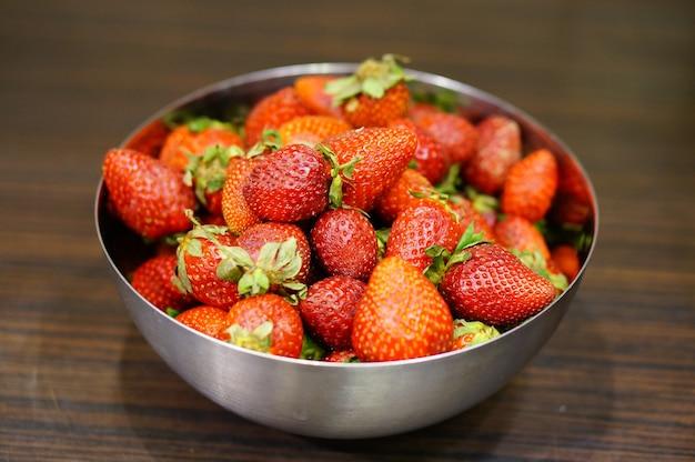Nahaufnahmeaufnahme einer schüssel der süßen roten erdbeeren auf einem holztisch Kostenlose Fotos