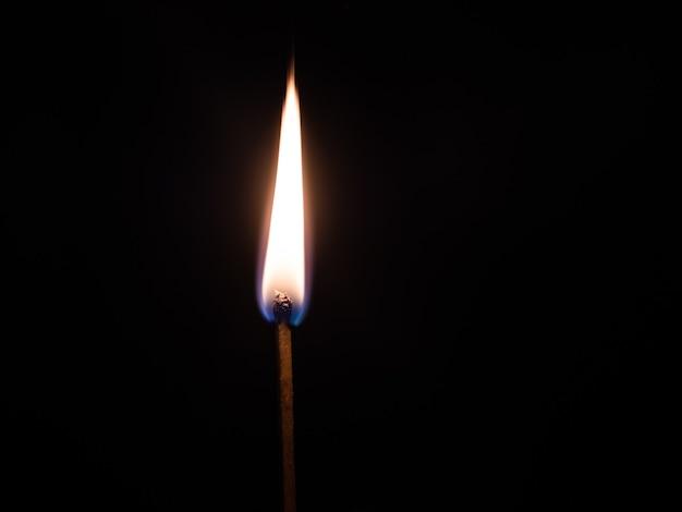 Nahaufnahmeaufnahme eines beleuchteten streichholzes mit einem schwarzen hintergrund Kostenlose Fotos