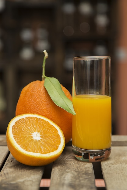 Nahaufnahmeaufnahme eines glases orangensaft und der frischen orangen auf einer holzkiste mit unschärfe Kostenlose Fotos