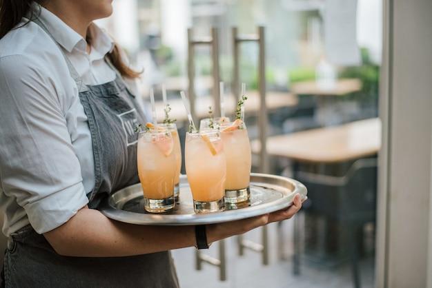 Nahaufnahmeaufnahme eines kellners, der cocktail mit frischen orangen auf einem silbernen tablett dient Kostenlose Fotos