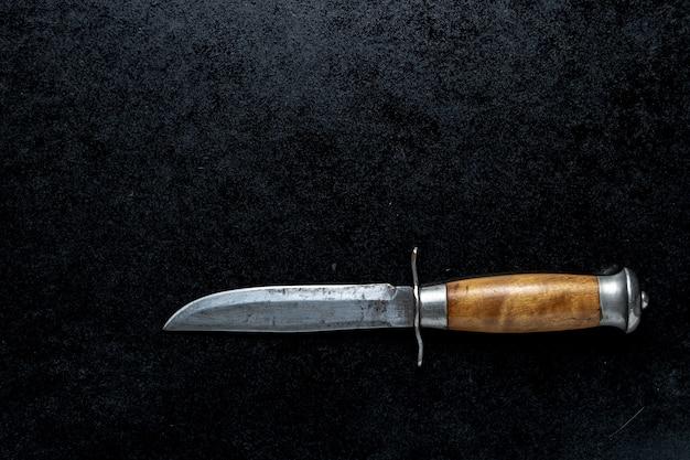 Nahaufnahmeaufnahme eines kleinen scharfen messers mit einem braunen griff auf einem schwarzen hintergrund Kostenlose Fotos