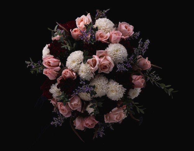 Nahaufnahmeaufnahme eines luxuriösen blumenstraußes von rosa rosen und weißen, roten dahlien auf einem schwarzen hintergrund Kostenlose Fotos
