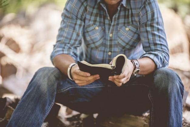 Nahaufnahmeaufnahme eines mannes in der freizeitkleidung, die die heilige bibel auf einem unscharfen hintergrund liest Kostenlose Fotos