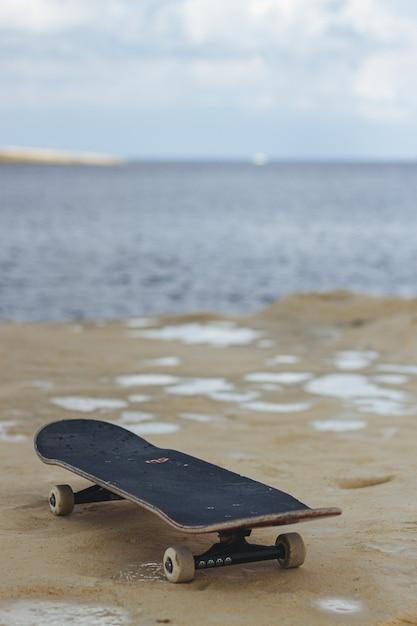 Nahaufnahmeaufnahme eines schwarzen skateboards auf dem nassen sand Kostenlose Fotos