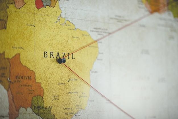 Nahaufnahmeaufnahme eines schwarzen stiftes auf dem brasilianischen land auf der karte Kostenlose Fotos