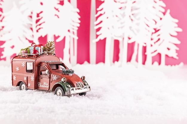 Nahaufnahmeaufnahme eines spielzeugautos für weihnachtsdekoration auf schnee Kostenlose Fotos