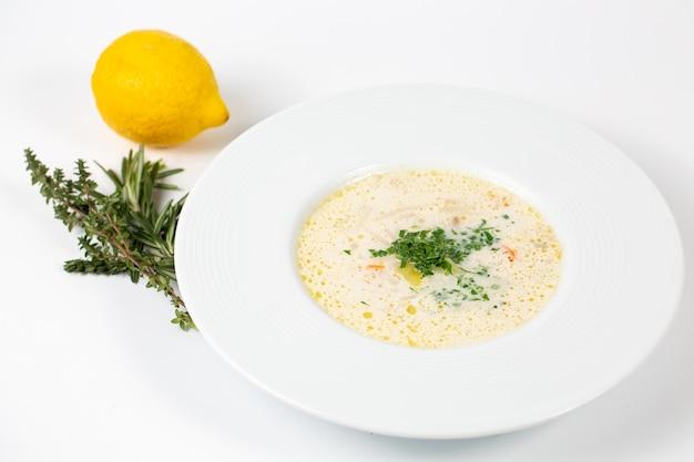 Nahaufnahmeaufnahme eines tellers mit weißer suppe mit grüns Kostenlose Fotos
