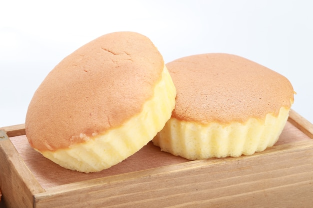 Nahaufnahmeaufnahme von zwei köstlichen frisch gebackenen cupcakes auf einer holzkiste Kostenlose Fotos