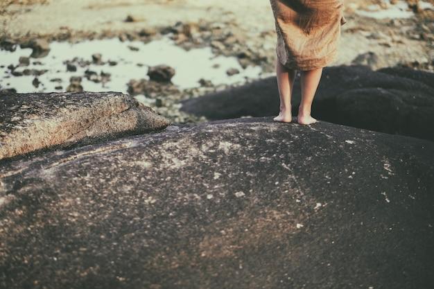 Nahaufnahmebild der beine einer frau beim stehen auf dem felsen durch den strand Premium Fotos