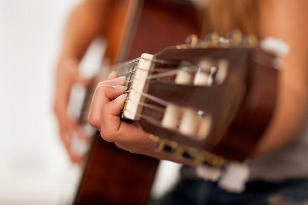 Nahaufnahmebild der gitarre in den frauenhänden Kostenlose Fotos
