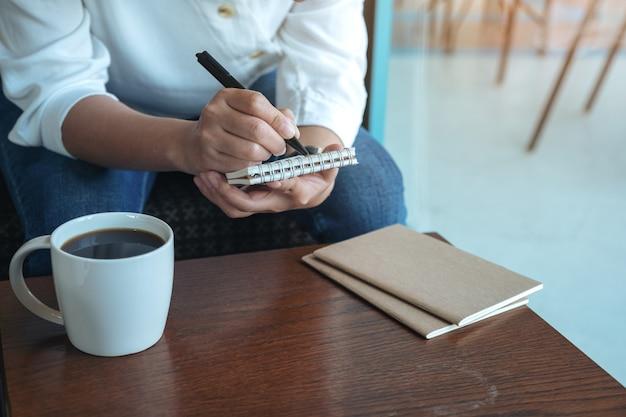 Nahaufnahmebild der hände einer frau, die auf leerem notizbuch mit kaffeetasse auf holztisch halten und schreiben Premium Fotos
