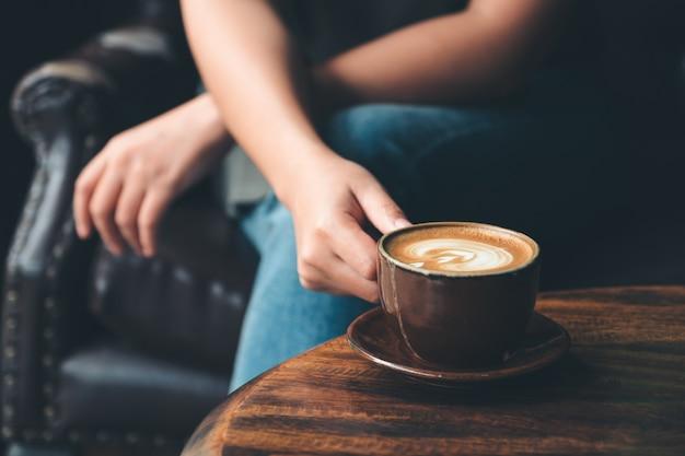 Nahaufnahmebild einer frau, die eine tasse kaffee auf weinleseholztisch im café hält Premium Fotos