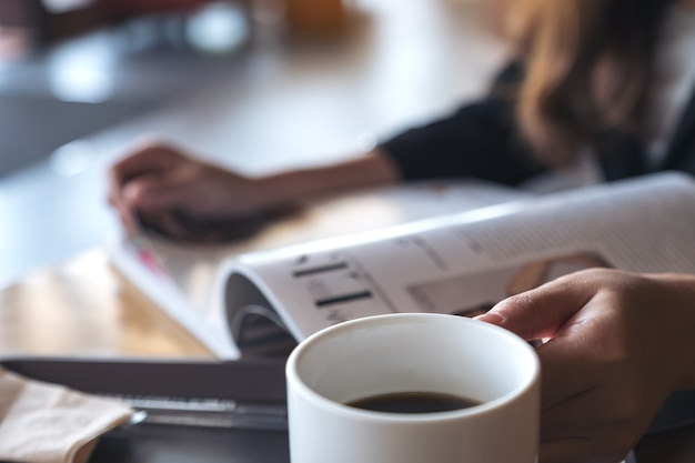 Nahaufnahmebild einer geschäftsfrau, die ein buch mit kaffeetasse auf tabelle im café liest Premium Fotos