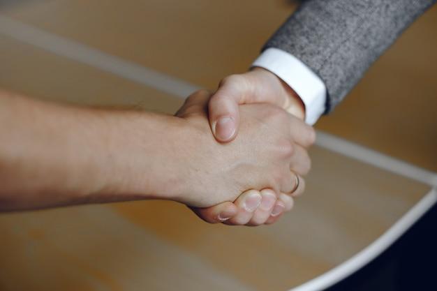 Nahaufnahmebild eines festen händedrucks. mann, der für eine vertrauenswürdige partnerschaft steht. Kostenlose Fotos