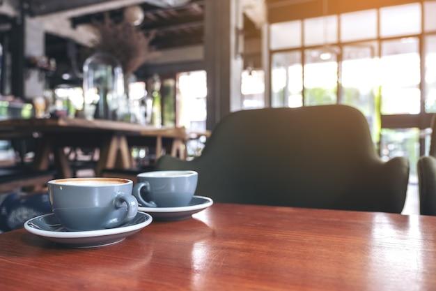 Nahaufnahmebild von zwei blauen tassen des heißen lattekaffees auf weinleseholztisch im café Premium Fotos