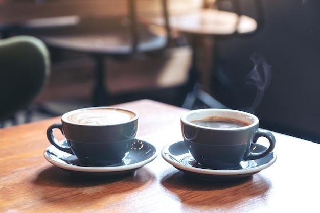 Nahaufnahmebild von zwei blauen tassen des heißen lattekaffees und des americano-kaffees auf weinlesetisch im weinlesetisch im café Premium Fotos