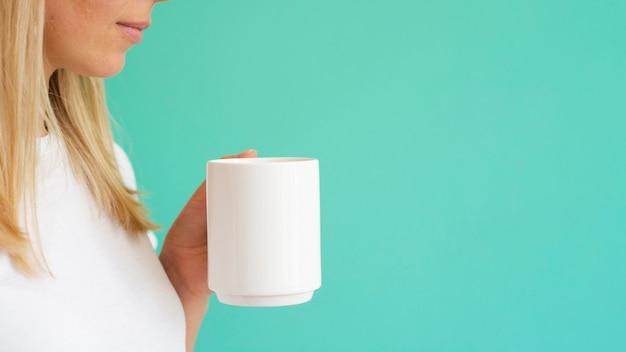 Nahaufnahmeblondine, die weißen becher halten Kostenlose Fotos