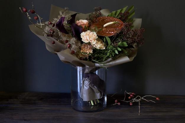 Nahaufnahmeblumenstrauß in einem glasvase verziert in der weinleseart auf einem dunklen hintergrund Premium Fotos