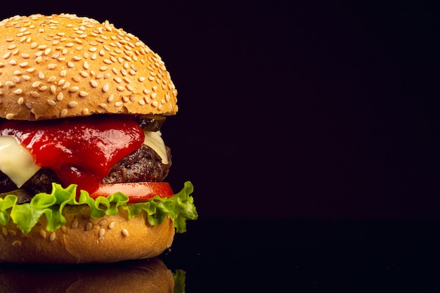 Nahaufnahmeburger mit schwarzem hintergrund Kostenlose Fotos