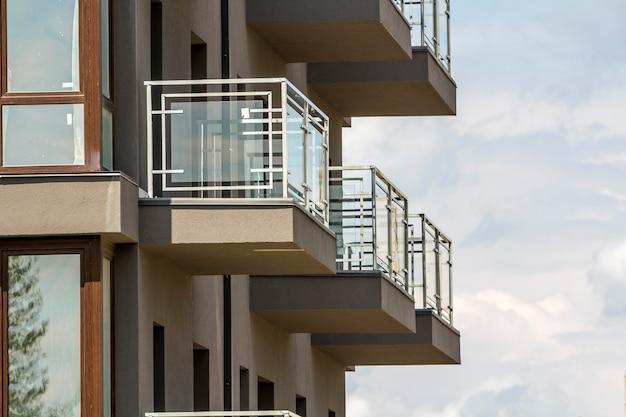 Nahaufnahmedetail der wohngebäudewand mit balkonen und glänzenden fenstern auf hintergrund des blauen himmels. Premium Fotos