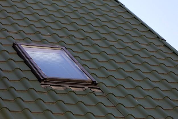 Nahaufnahmedetail des neuen kleinen dachbodenplastikfensters installiert in dunkelgrünes geschichtetes hausdach Premium Fotos