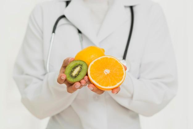 Nahaufnahmedoktor mit früchten und stethoskop Kostenlose Fotos