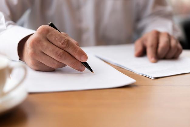 Nahaufnahmeerwachsener, der einen vertrag im büro unterzeichnet Kostenlose Fotos