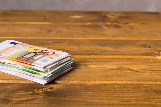 Nahaufnahmeeurobanknoten auf holztisch Premium Fotos