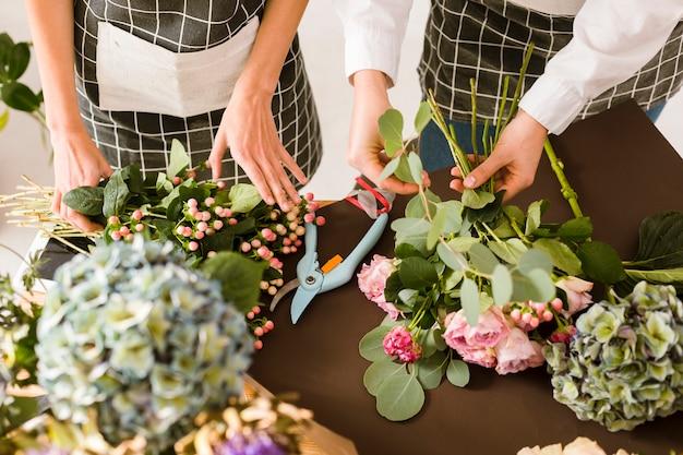 Nahaufnahmefloristen, die blumenstrauß mit rosa rosen machen Kostenlose Fotos