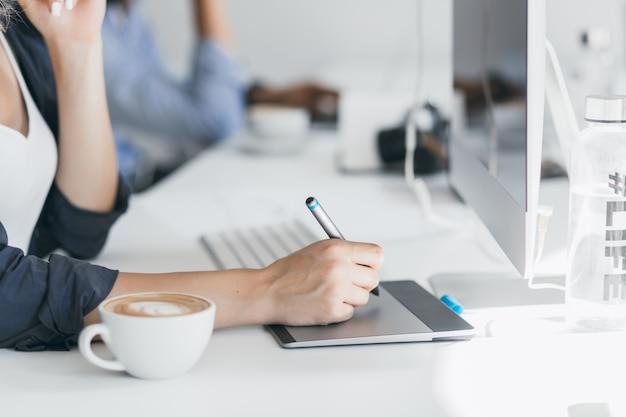 Nahaufnahmefoto der weiblichen hand, die stift auf tablette hält. innenporträt eines freiberuflichen webentwicklers, der während der kaffeepause im büro an einem projekt arbeitet. Kostenlose Fotos