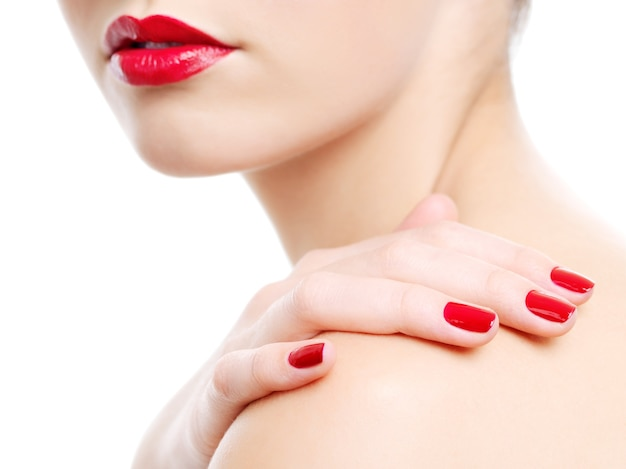 Nahaufnahmefoto einer schönen roten weiblichen lippen. hand mit schönheitsmaniküre auf einer schulter Kostenlose Fotos