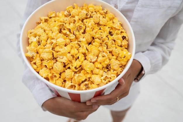 Nahaufnahmefoto eines jungen süßen mädchens, das eine tube popcorn in ihren händen hält. Kostenlose Fotos