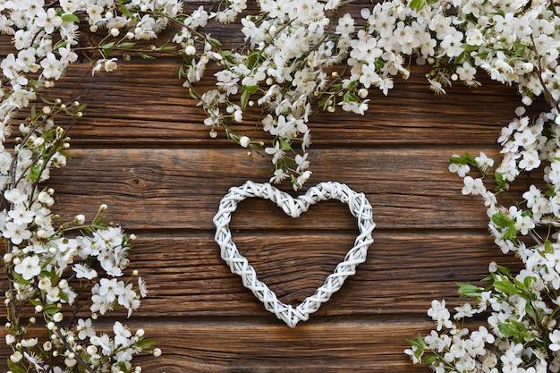 Nahaufnahmefoto von schönen weißen blühenden cherry tree-niederlassungen mit weißer herzform. Premium Fotos