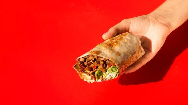 Nahaufnahmefrau, die burrito mit kopieraum hält Kostenlose Fotos