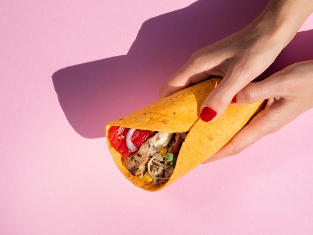 Nahaufnahmefrau, die burrito mit rosa hintergrund hält Kostenlose Fotos