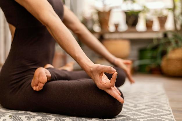 Nahaufnahmefrau, die drinnen meditiert Kostenlose Fotos