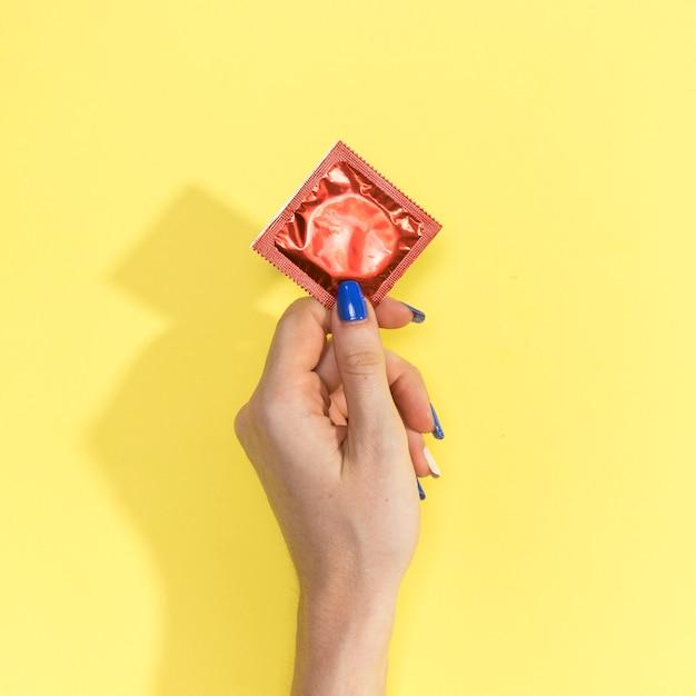 Nahaufnahmefrau, die ein kondom hält Kostenlose Fotos