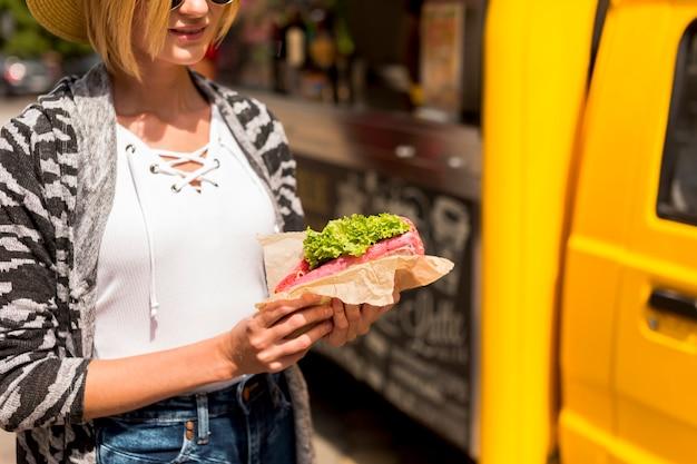 Nahaufnahmefrau, die ein sandwich hält Kostenlose Fotos